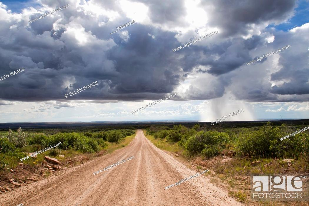 Stock Photo: Isolated thundershower falling from looming cumulus cloud formations while sun shines on dirt road leading into the distance.