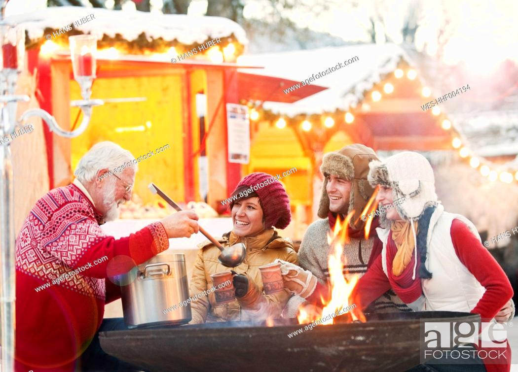 Stock Photo: Austria, Salzburg, Senior man serving drink to young people at christmas market, smiling.