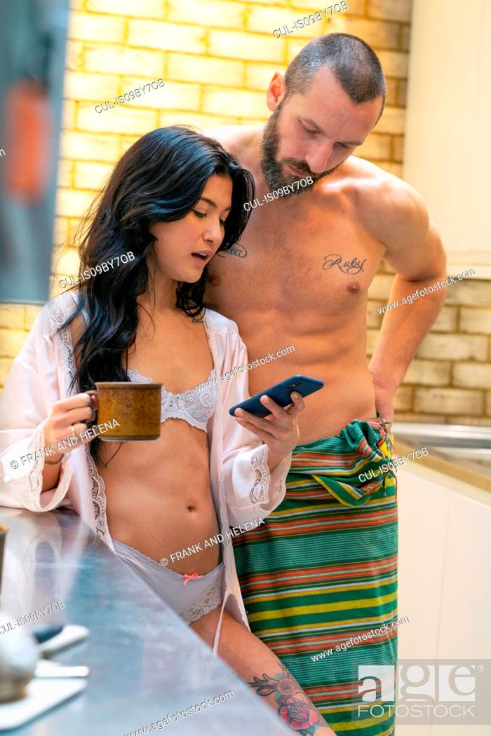 Stock Photo: Hipster couple using smartphone in kitchen.