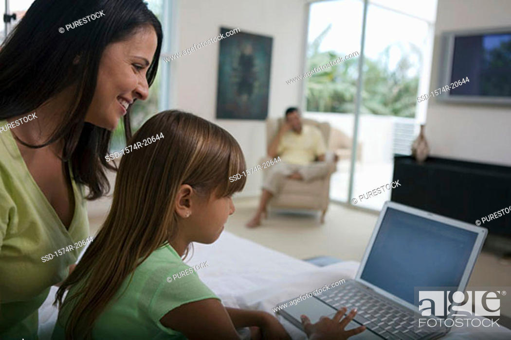 Stock Photo: Side profile of a girl using a laptop with her mother sitting behind her.