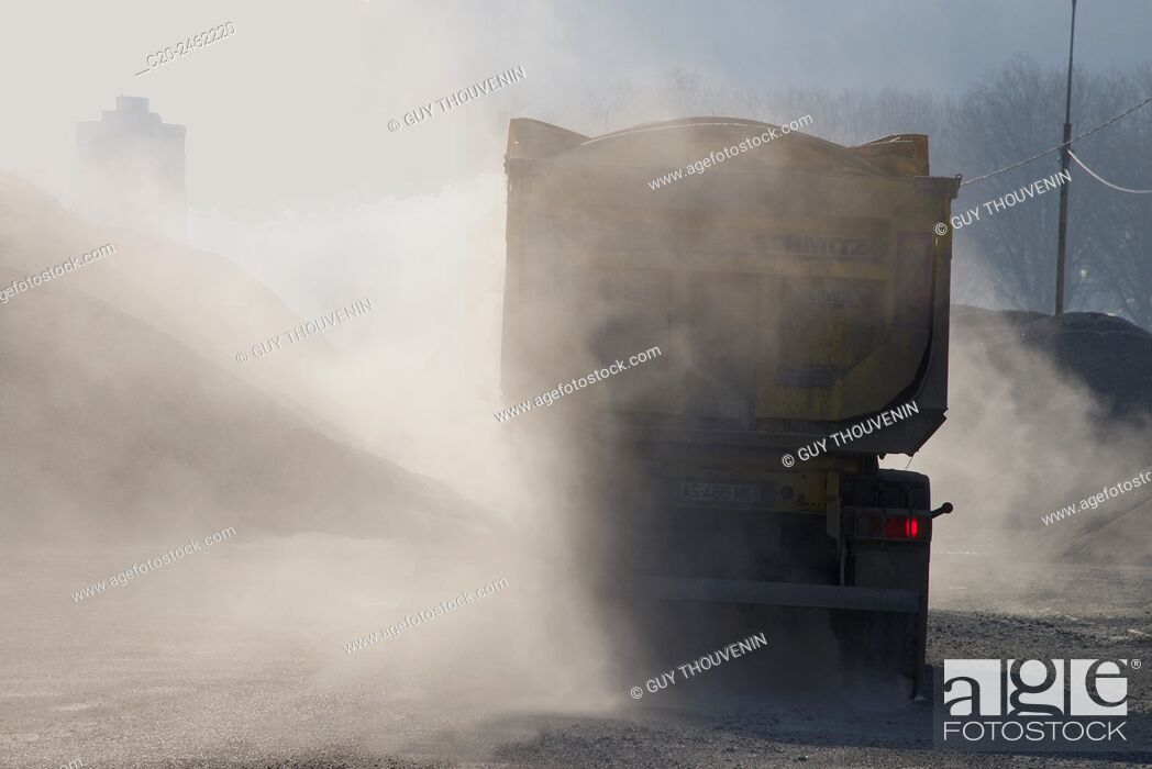 Stock Photo: Lorry, truck transporting stones, with red brake light, through dust, France.