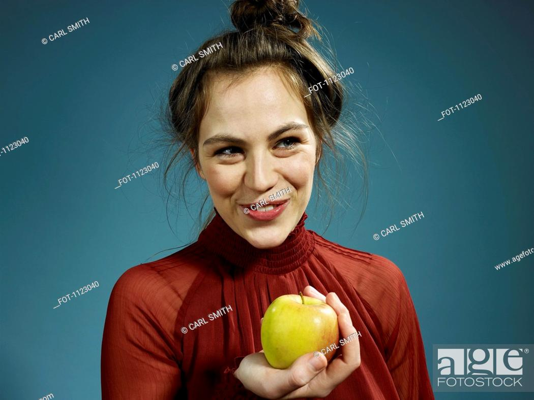 Stock Photo: A hip young woman holding an apple and smiling.
