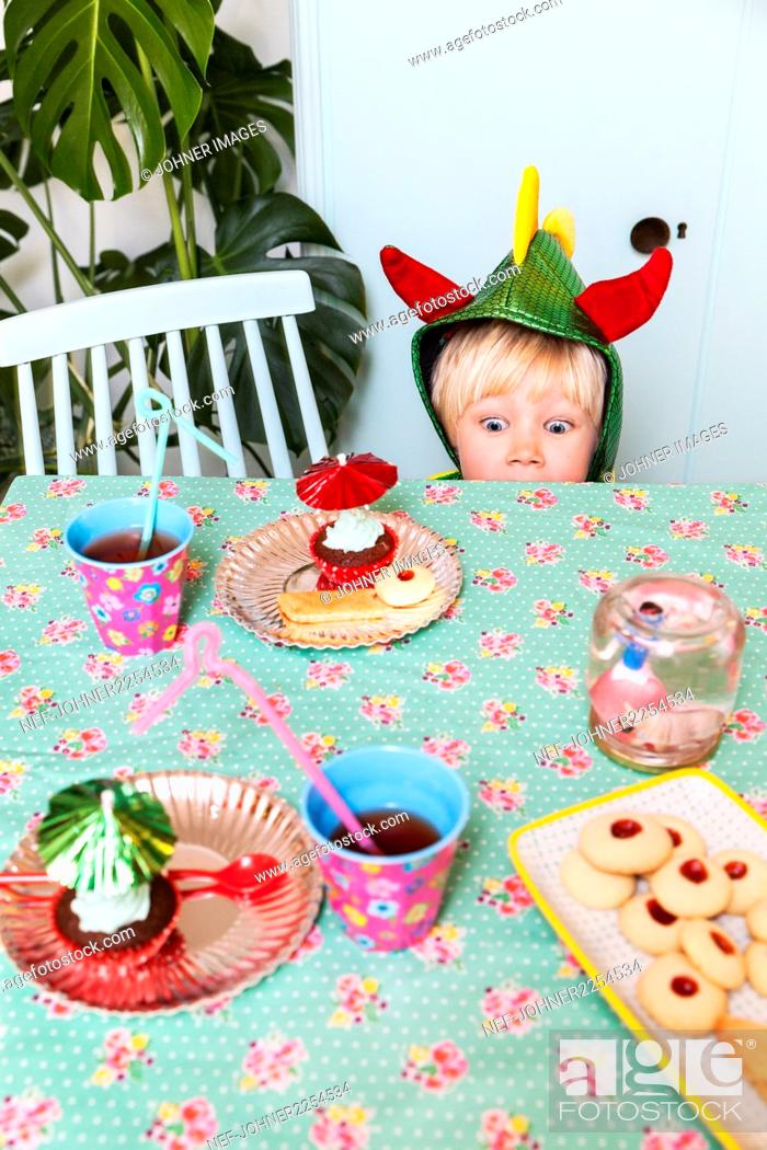 Stock Photo: Boy looking at sweets on table.