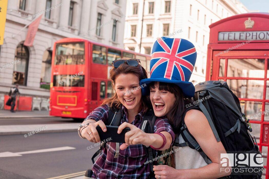 Stock Photo: Two women backpackers wearing union jack hat taking smartphone selfie, London, UK.