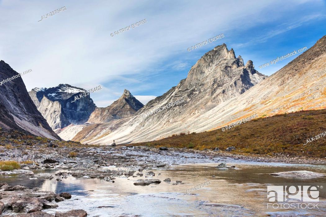 Stock Photo: Hiker on a large boulder in Arrigetch Creek, morning light on Arial peak, Arrigetch Peaks, Gates of the Arctic National Park, Alaska.