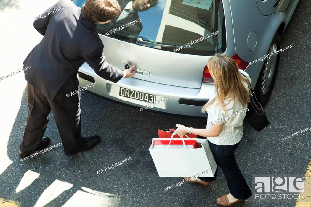 Stock Photo: Couple opening car hatchback to stow shopping bags.
