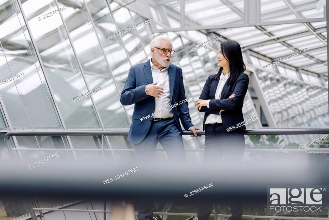 Imagen: Businessman and businesswoman talking in modern office building.