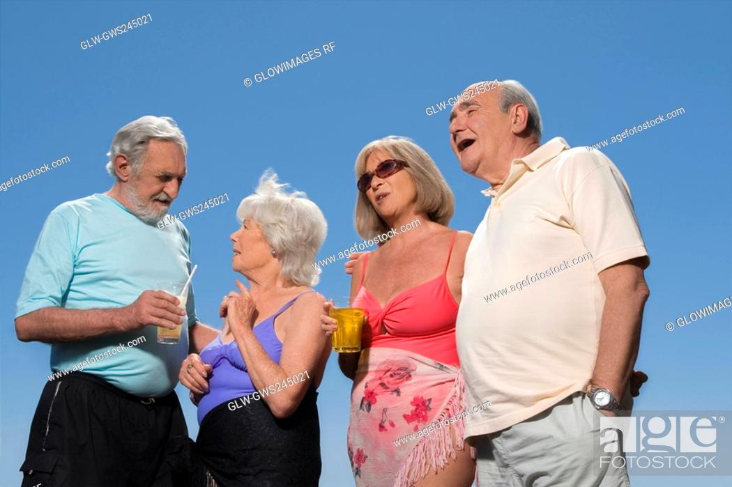 Stock Photo: Low angle view of two senior couples standing together.