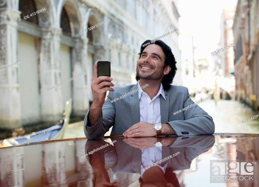 Stock Photo: Smiling businessman holding cell phone and leaning on boat in canal in Venice.
