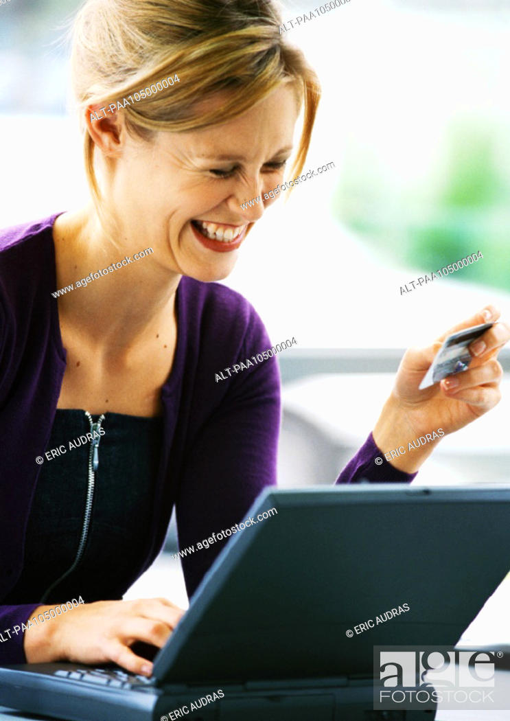 Stock Photo: Woman using laptop computer and holding credit card, laughing.