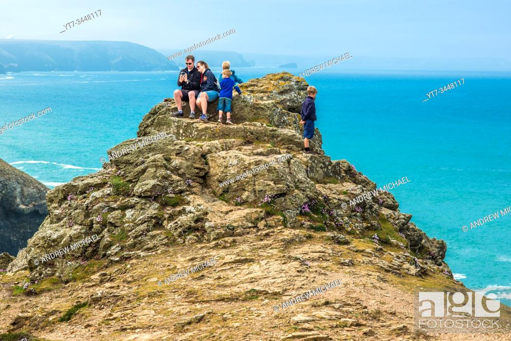 Stock Photo: A family on the rocks above Chapel Porth on the St Agnes Heritage coast in Cornwall, England, UK.