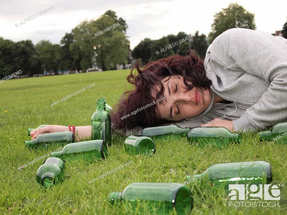 Stock Photo: Woman lying over grass with bottles.