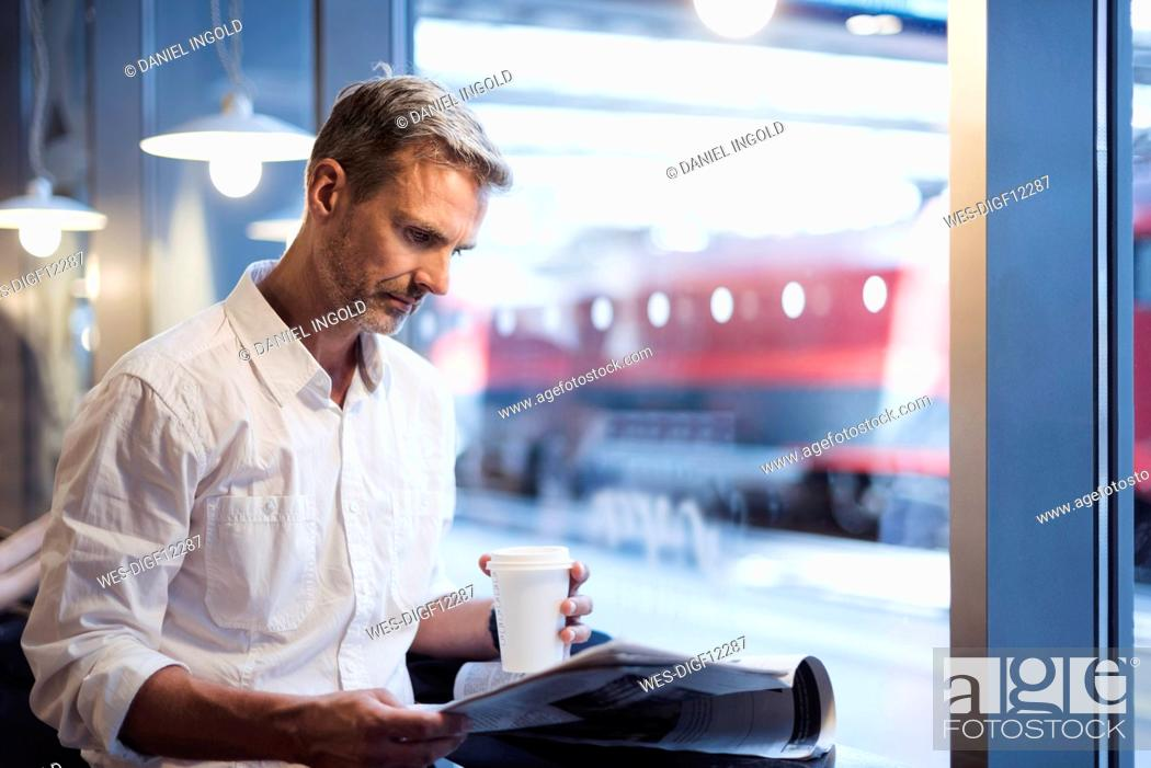 Imagen: Businessman holding coffee reading newspaper while sitting in train.