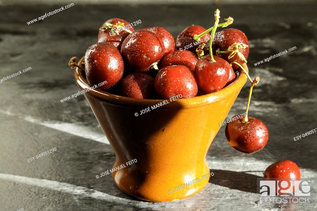 Stock Photo: cherry bowl on dark marbled background with natural light.
