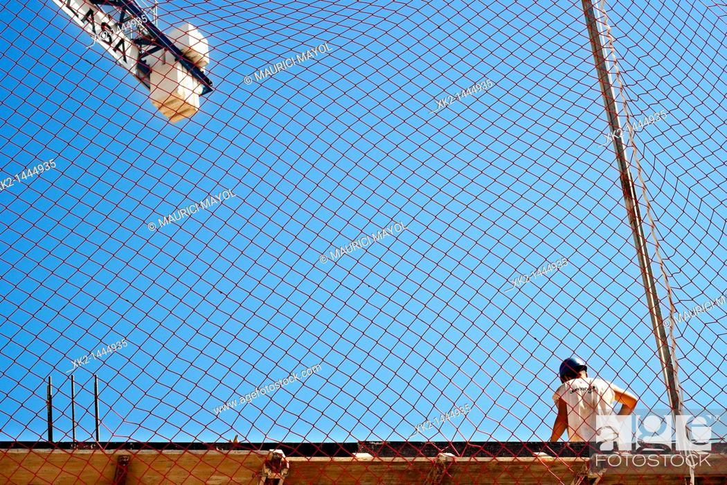 Stock Photo: Prevención de riesgos laborales, trabajador de la construcción ante una red de seguridad.