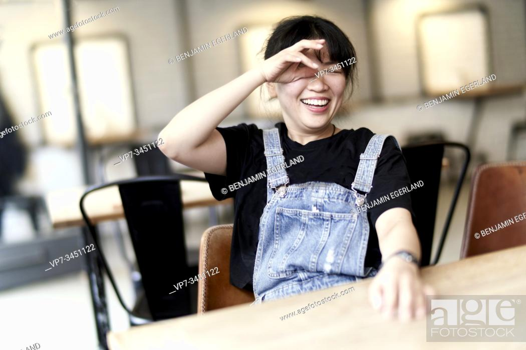 Stock Photo: Korean woman sitting at table in cafe, laughing.