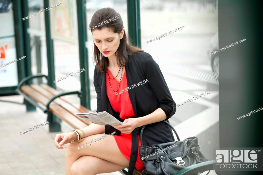 Stock Photo: Woman sitting at bus stop and reading a newspaper.