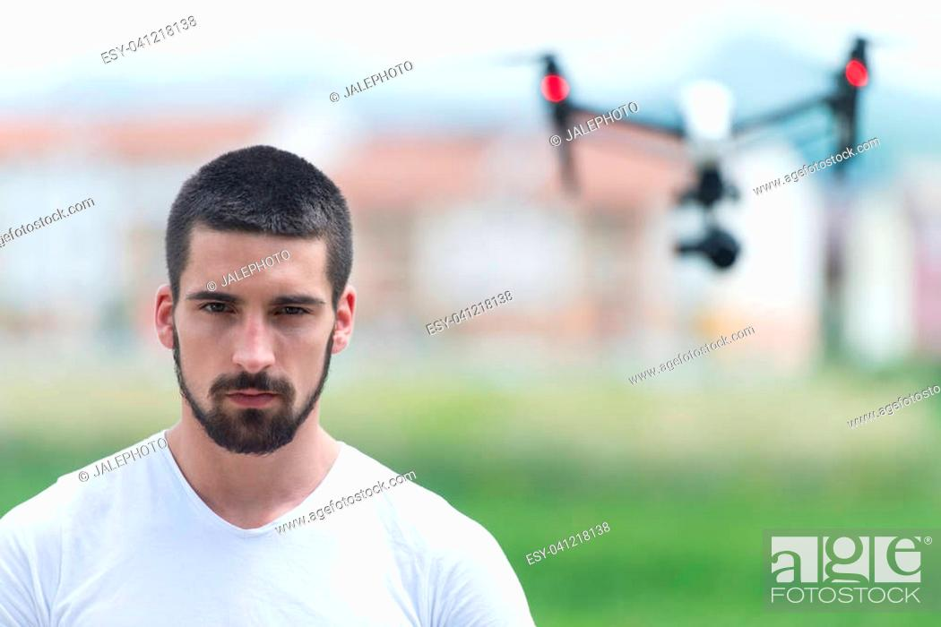 Stock Photo: Man Operating Drone Flying or Hovering by Remote Control in Nature.