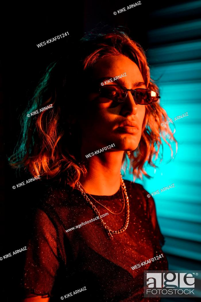 Stock Photo: Stylish young woman at night in front of roller shutter, wearing sunglasses.