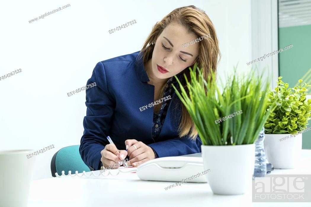 Stock Photo: Tired woman sitting and writing in the coworking space. Horizontal indoors shot.