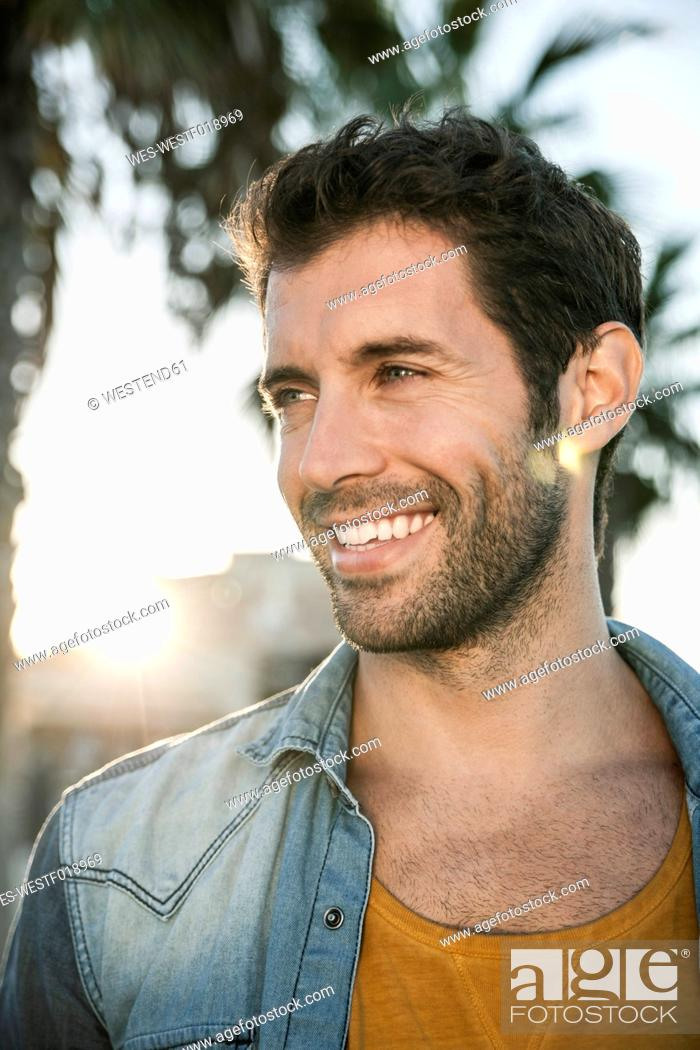 Stock Photo: Spain, Mid adult man looking away, smiling.