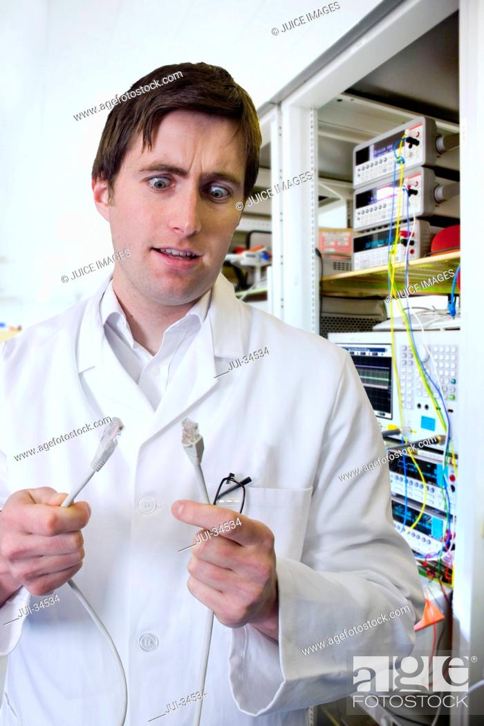 Stock Photo: Wide-eyed engineer holding computer data cable in laboratory.