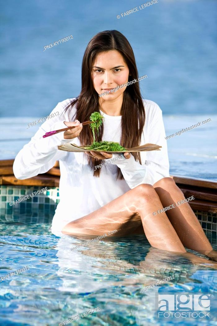 Stock Photo: Woman eating seaweed with chopsticks.