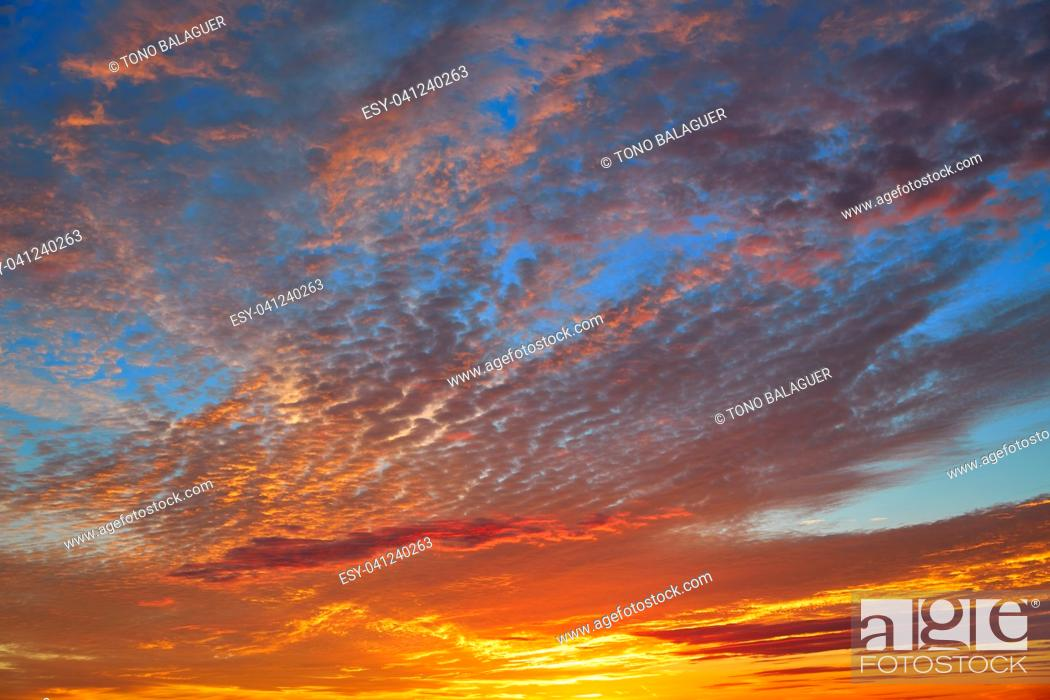 Photo de stock: Sunset sky with orange clouds over blue background.