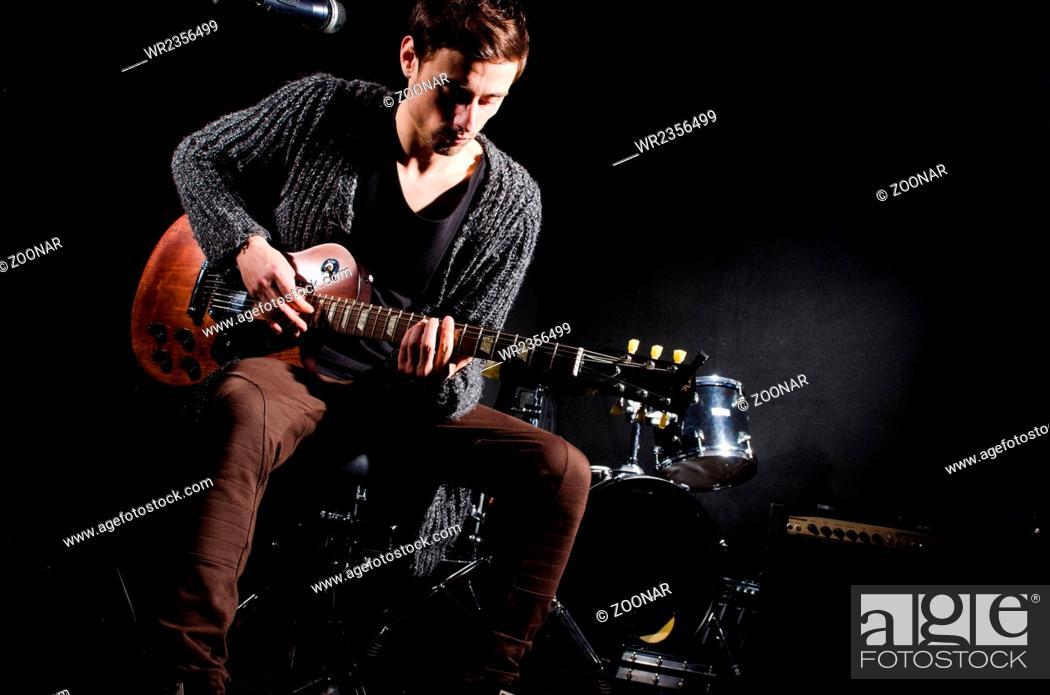 Imagen: Man playing guitar in dark room.