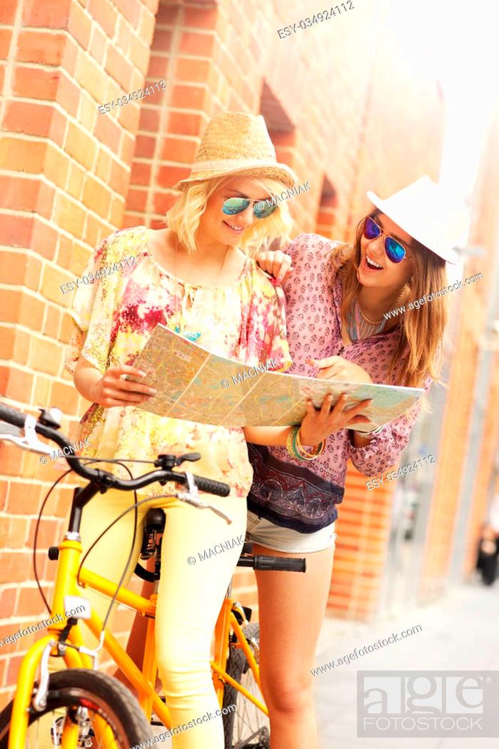 Stock Photo: A picture of two girl friends using a map and riding a tandem bicycle in the city.