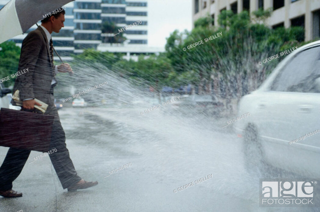 Stock Photo: businessman gets splashed by a passing car.