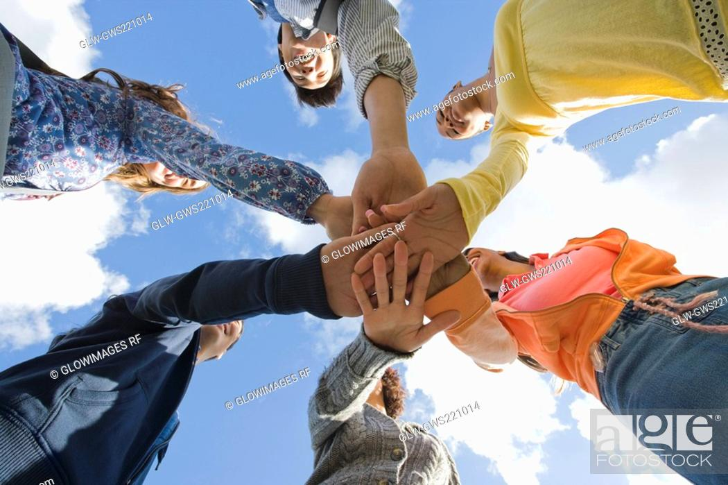 Stock Photo: Low angle view of university students stacking their hands in a huddle.