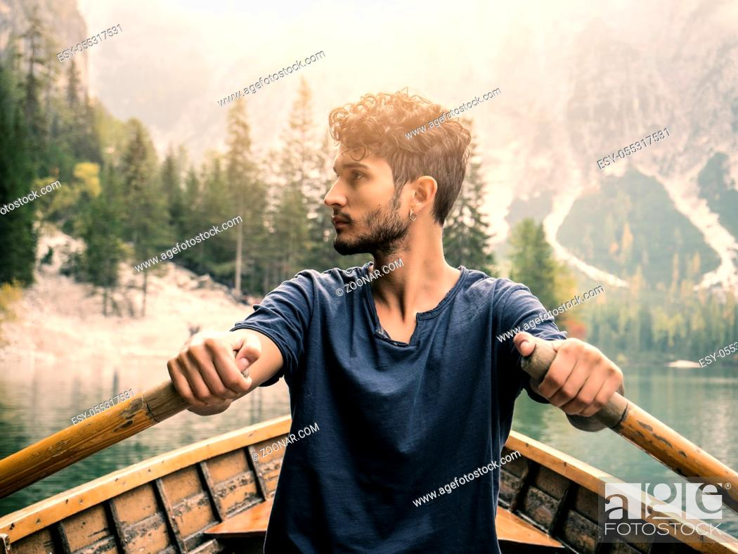 Photo de stock: Young casual man sitting in boat and rowing while looking away on background of lake and mountains.