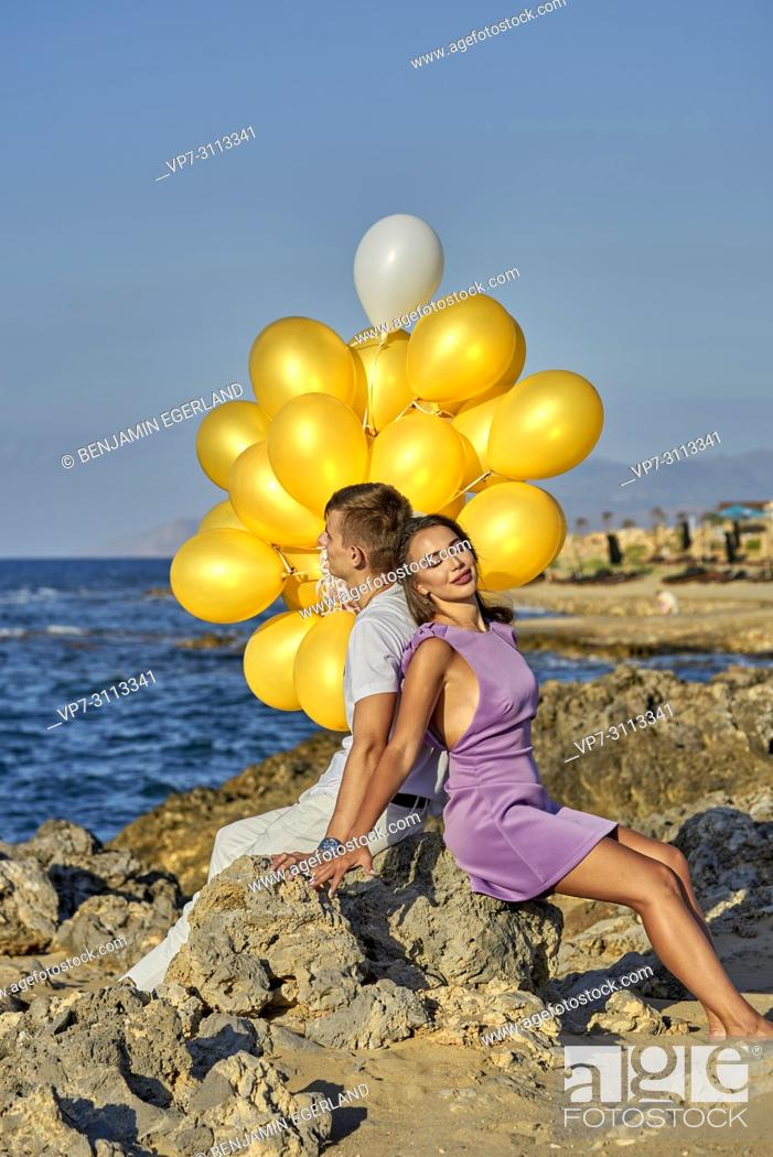 Photo de stock: couple sitting at seaside, leaning against each other, with balloons.