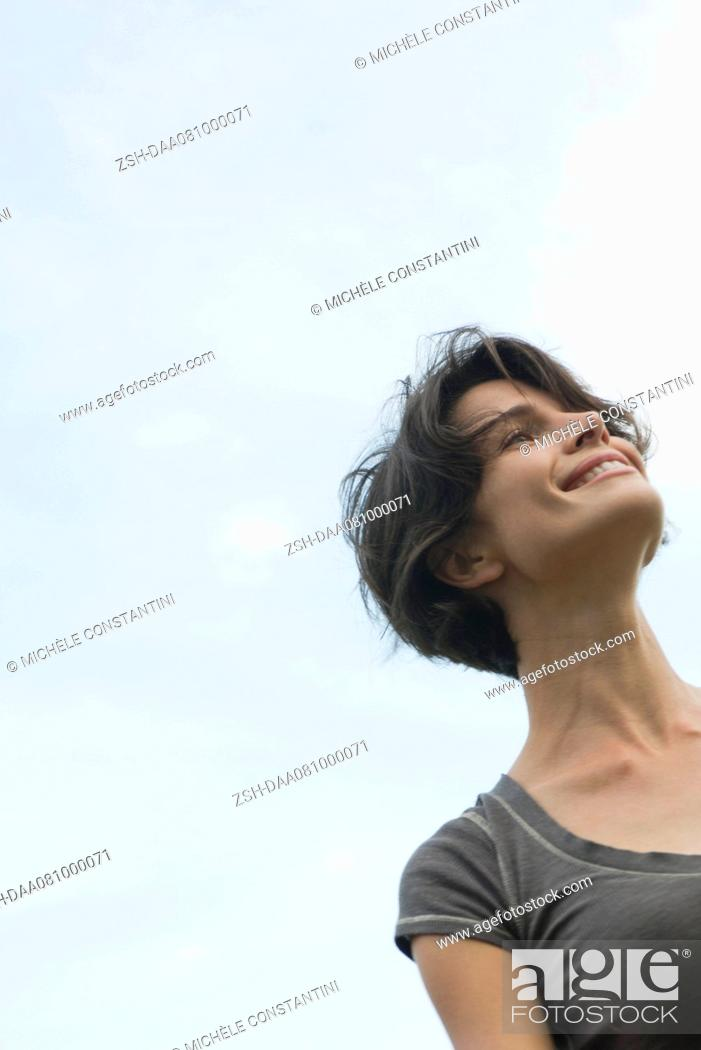 Stock Photo: Woman smiling outdoors, low angle view.
