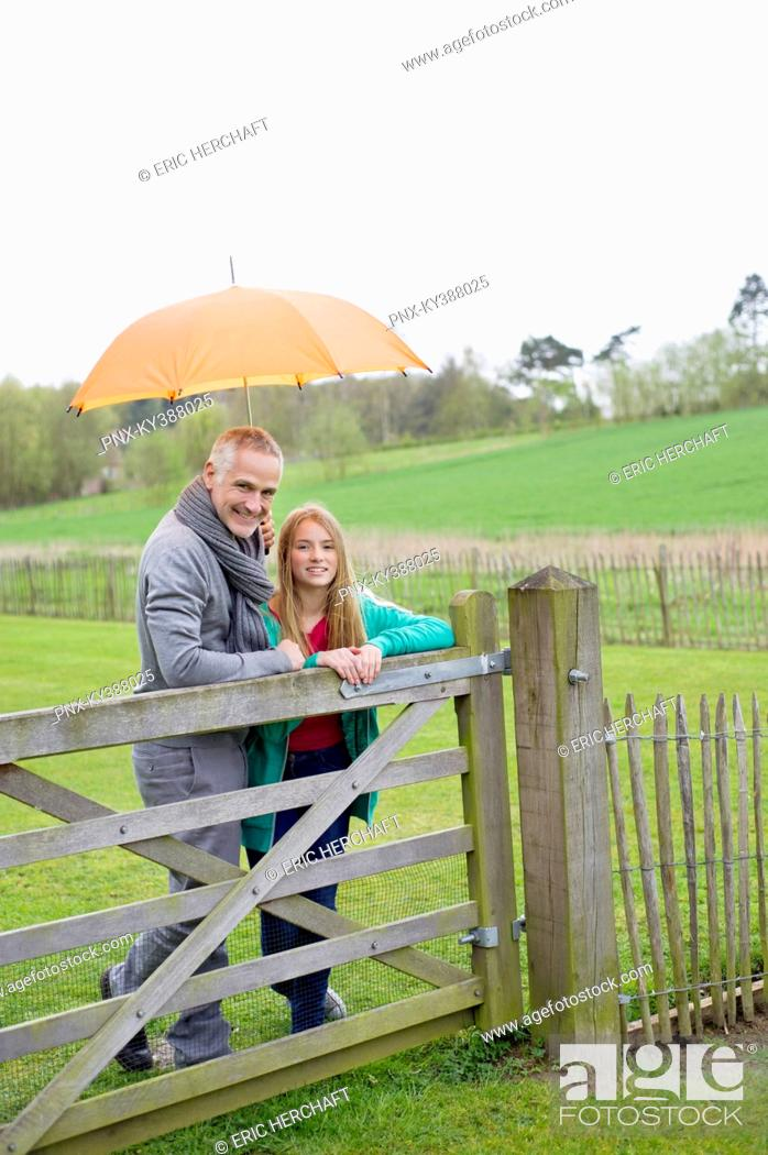 Stock Photo: Man standing with his daughter in a farm with an umbrella.