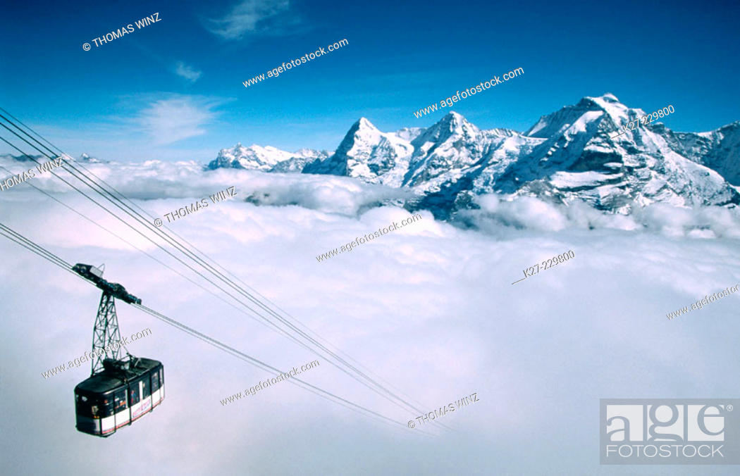 Stock Photo: Cable railway appearing through fog. Eiger and Mönch peaks. Alps. Switzerland.