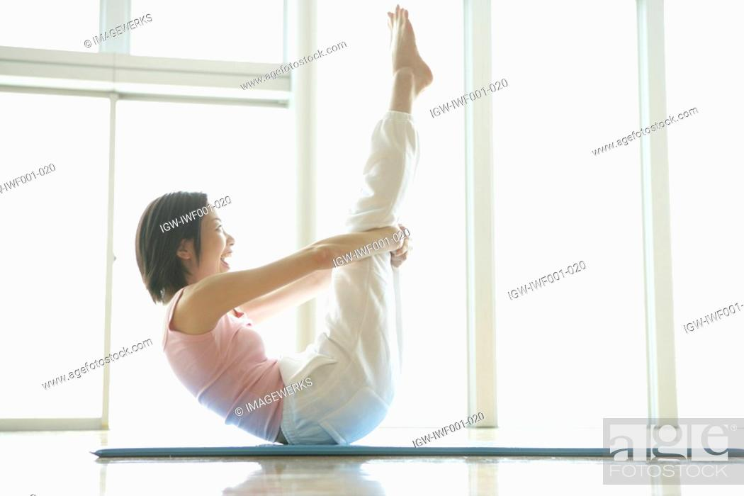 Stock Photo: A young woman is elated as she holds her legs straight up in the air.