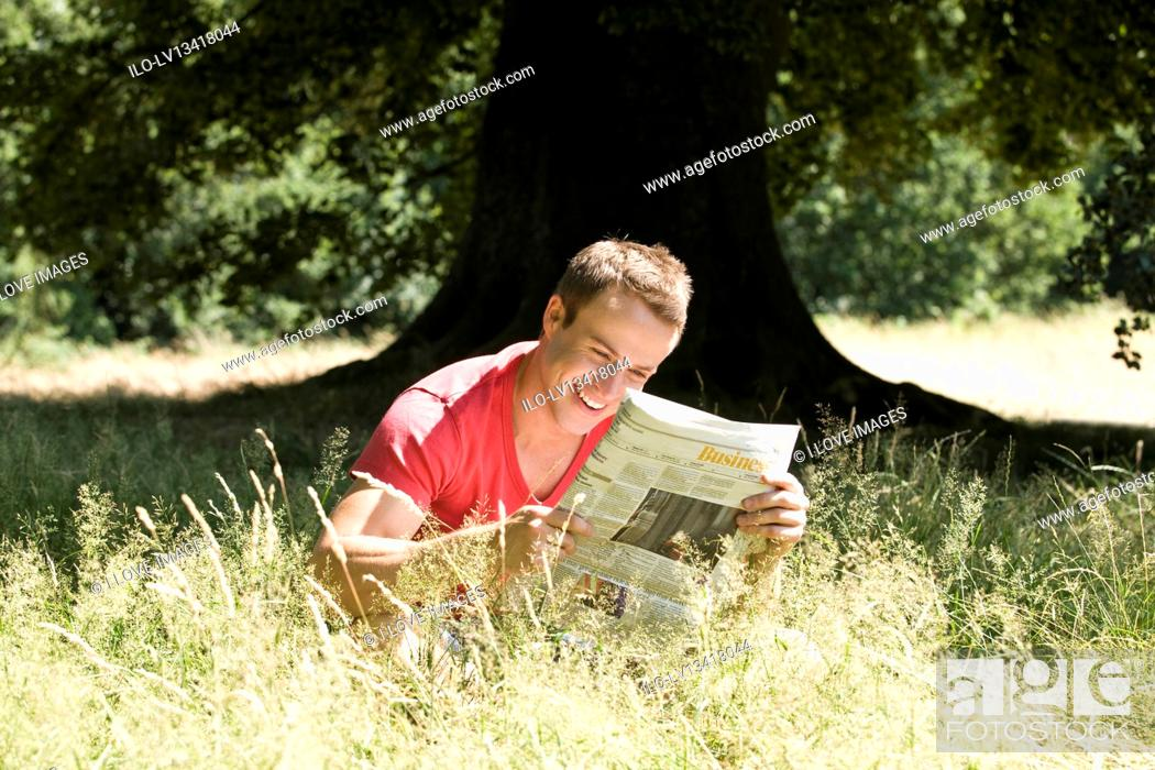 Stock Photo: A young man sitting on the grass, reading a newspaper.