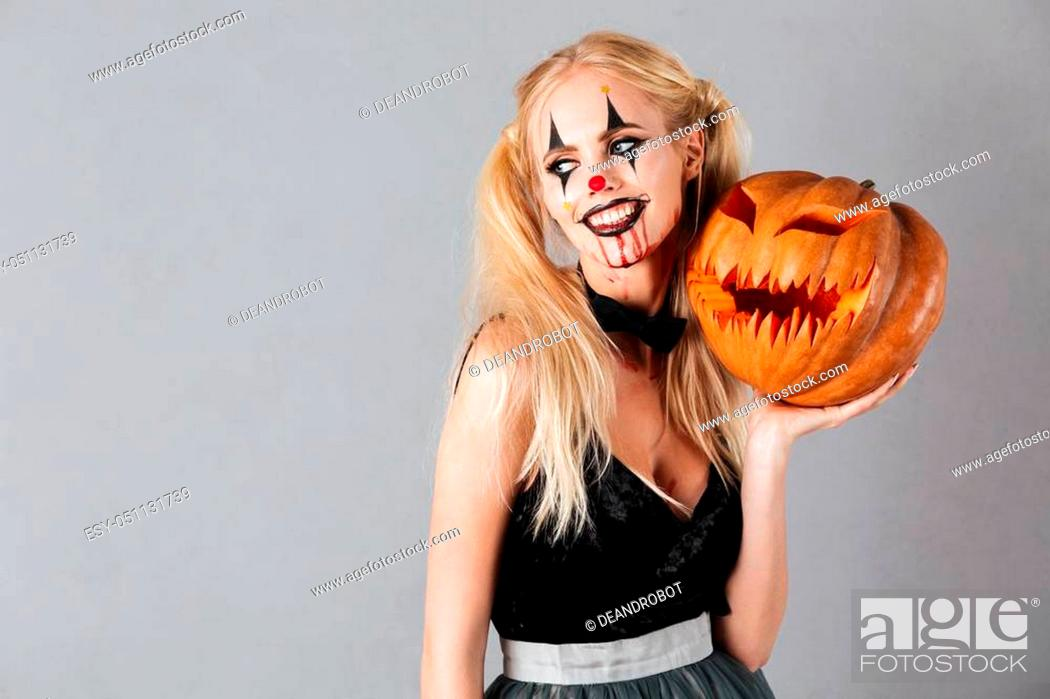 Stock Photo: Smiling blonde woman in halloween make up posing with carved pumpkin and looking away over gray background.