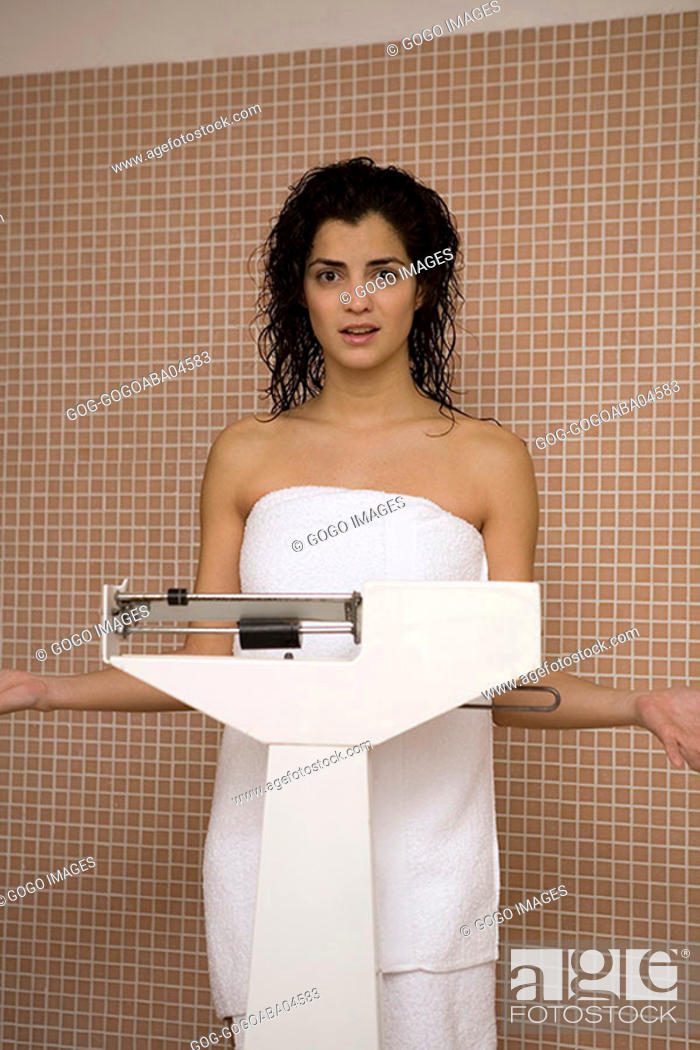 Stock Photo: Woman wrapped in a towel weighing herself.