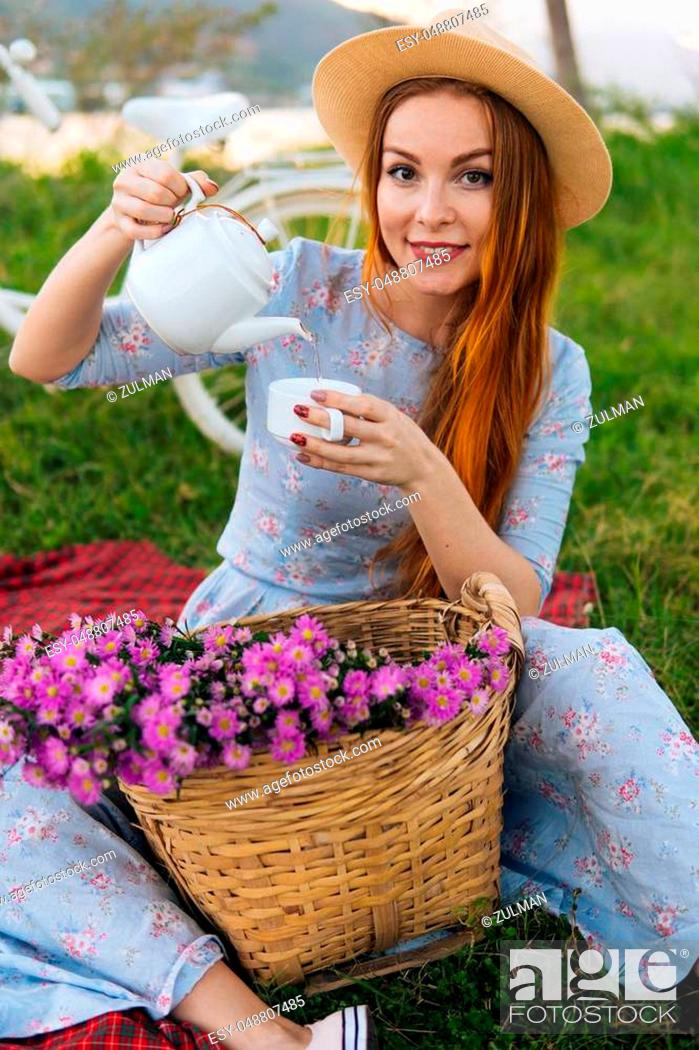 Stock Photo: Woman in long dress and hat pouring tea, enjoying picnic. Female drink tea outdoors. Bicycle on background.