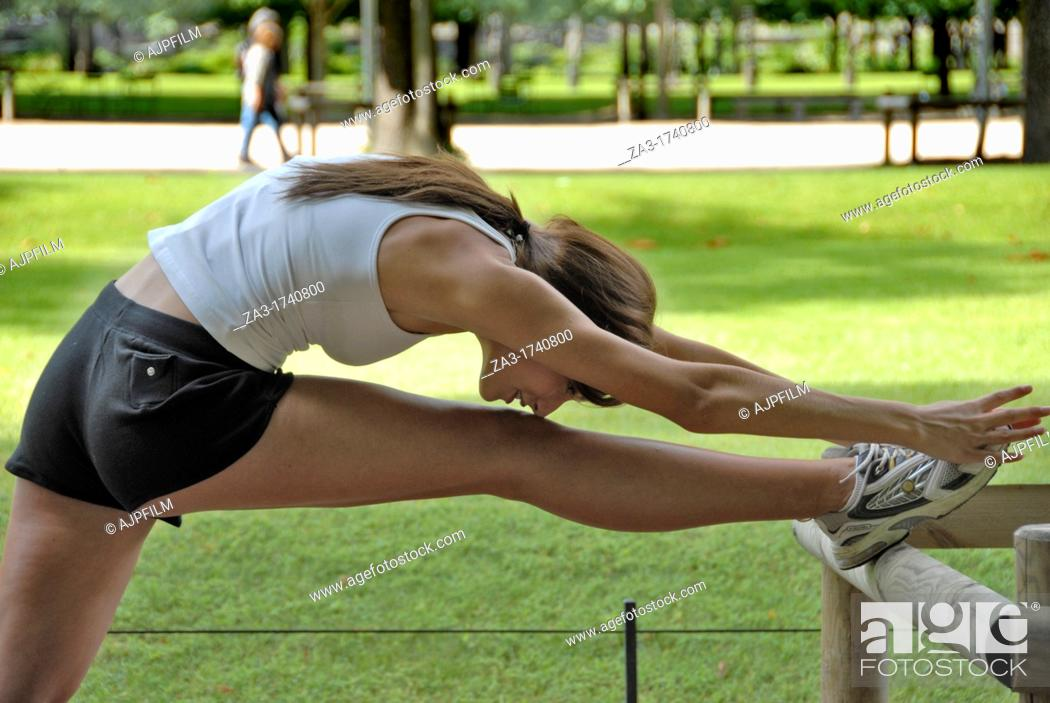 Stock Photo: 20 years old runner stretching in park.