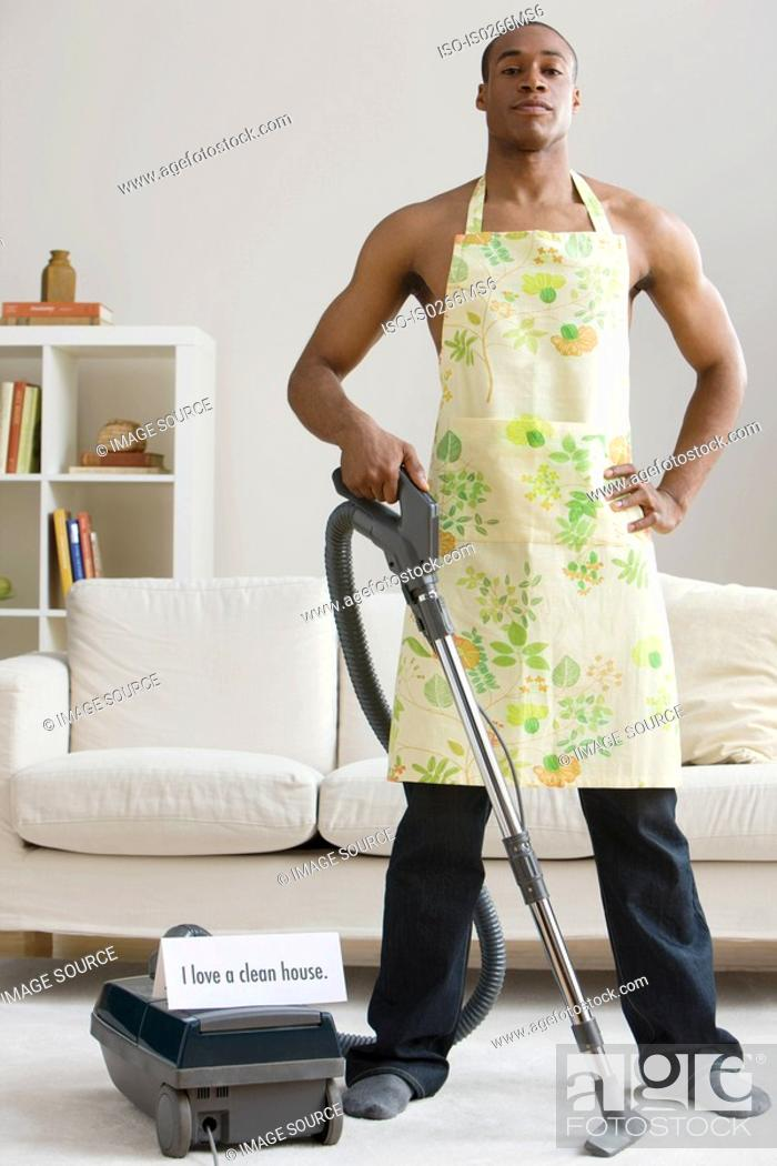 Stock Photo: A man vacuum cleaning.