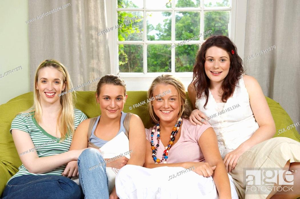 Stock Photo: Four young women seated on couch.