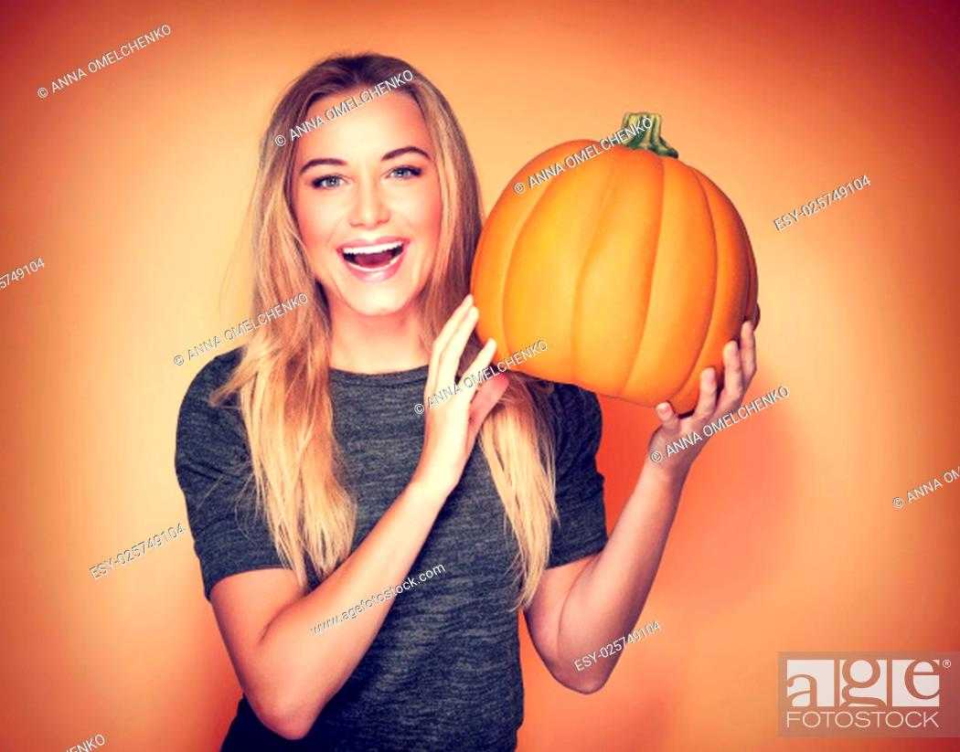 Stock Photo: Portrait of beautiful cheerful woman with pumpkin over orange background, celebrating happy Thanksgiving day.