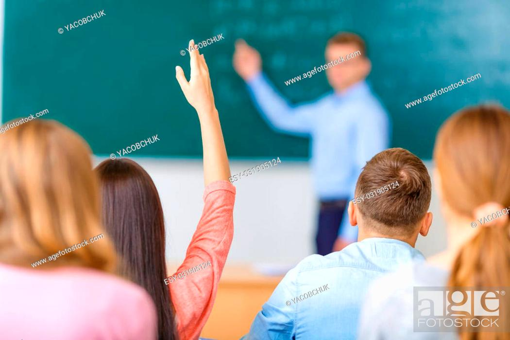 Stock Photo: Desire to answer. Female young student in a group raises her arm in order to answer the question.