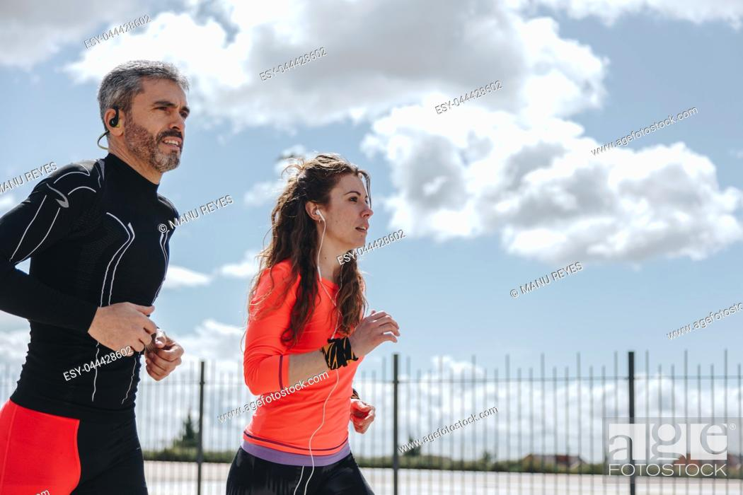 Imagen: young adults couple running together in the street.