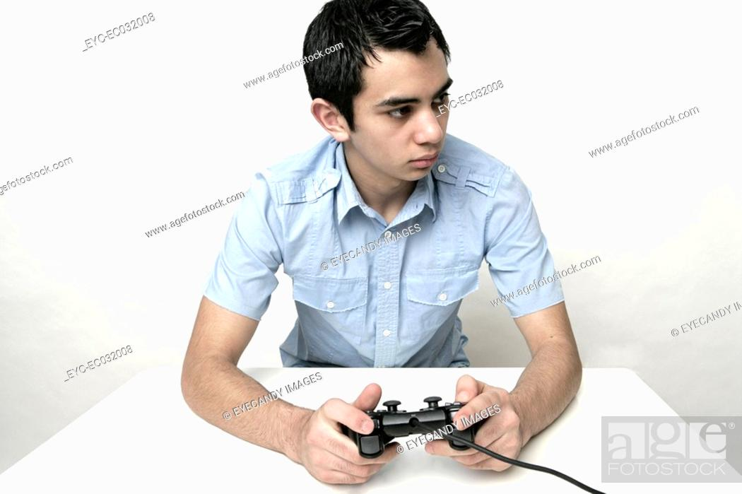 Stock Photo: View of a teenage boy holding a control.