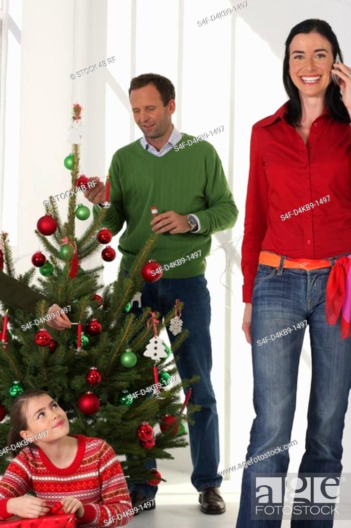 Stock Photo: Family in Christmassy room, mother phoning with a mobile phone, father decorating the Christmas tree.